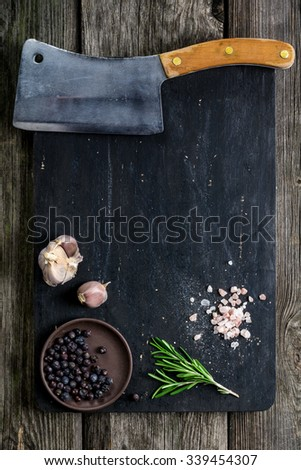 Old cleaver (butcher meat knife) and spices on wooden cutting board, texture background. Cooking ingredients. Copy space. Mock up for cook book - stock photo