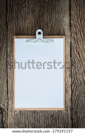 Old clipboard on grungy wooden surface, with plenty of copy space.Photo retro style - stock photo