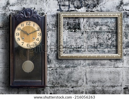 Old clock and empty picture frame on grunge wall. - stock photo
