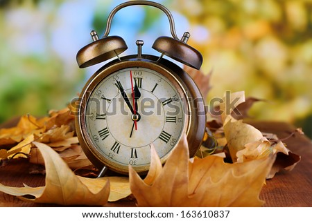 Old clock on autumn leaves on wooden table on natural background - stock photo