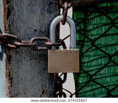 Old closed padlock on the rusty iron gate - stock photo