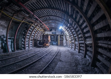 Old coal cart on tracks in mine - stock photo