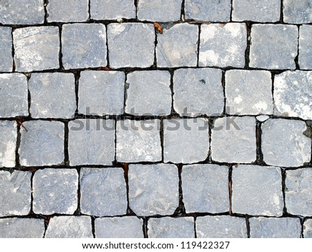 Old cobblestone road. Abstract background. Close up. - stock photo