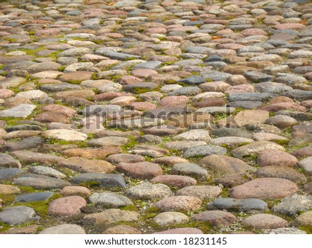 Old cobblestone road close up, with some grass - stock photo