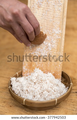 Old coconut pulp grated on wooden shredder - stock photo