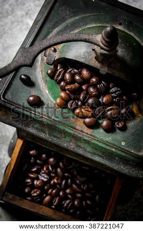 Old coffee grinder and roasted coffee . Close-up.  - stock photo
