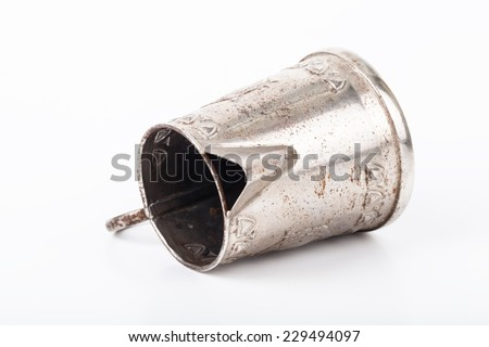 Old coffee pot without cover with spots of rust lying on its side on a white background. Sharpness on the spout - stock photo