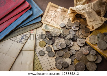 Old coins and bank book on grunge background. - stock photo