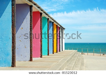 old colorful beach huts in a row with blue sky and clouds - stock photo