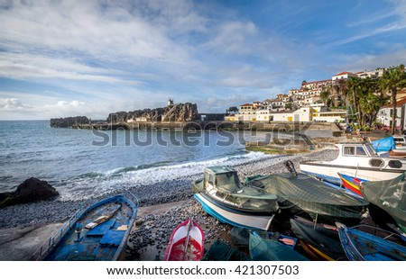 Old colorful fishing boats laying on the shore in Camara de Lobos fisherman's village. Popular touristic town in Madeira island, Portugal. - stock photo