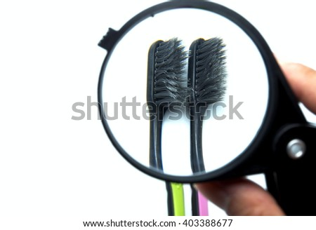 Old colorful toothbrushes with black magnifying glass on white background. Space for texts. - stock photo