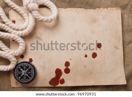 old compass and rope on the old paper background from old fabric - stock photo