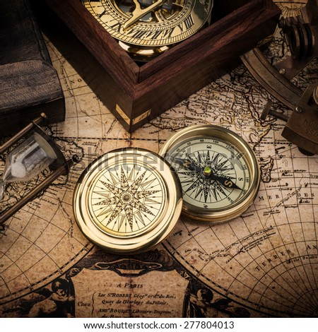 Old compass, astrolabe on vintage map. Retro stale. - stock photo