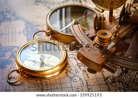 Old compass, astrolabe on vintage map. Retro stale. Very shallow focus. - stock photo