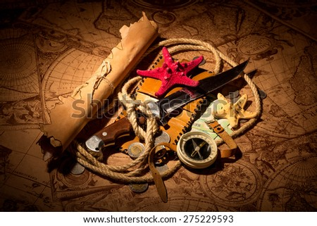 Old compass lying on antique map with rope, knife, money,globe and starfishes - stock photo