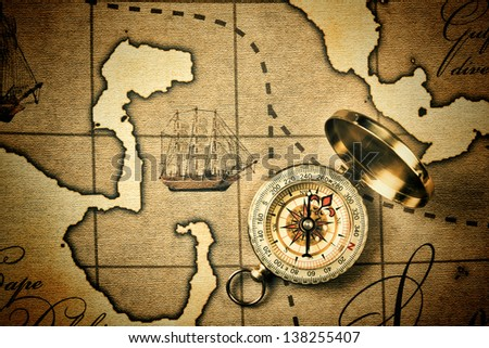 Old compass on a stylized map - stock photo