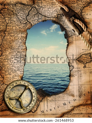 Old compass on vintage burned-down map opens a view of the sea. Ready design on the subject of adventures, pirates - stock photo