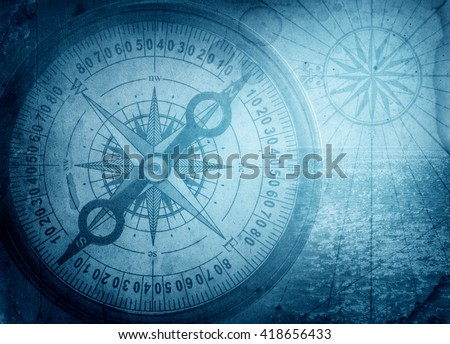 Old compass on vintage map. Pirate and nautical theme grunge background. - stock photo