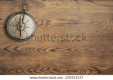 old compass on vintage wooden table top view - stock photo