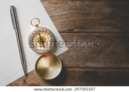Old compass on white paper and vintage map. Retro stale - stock photo