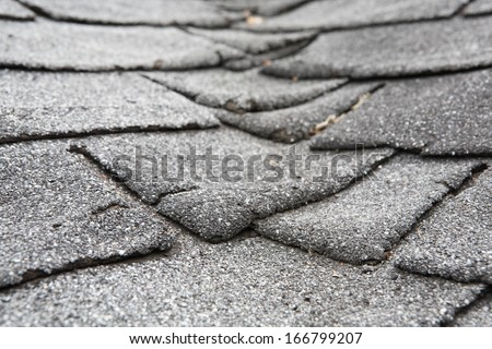 Old composite  roof with damage - stock photo