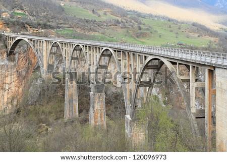Old concrete arch Bridge Djurdjevica Tara in Montenegro - stock photo