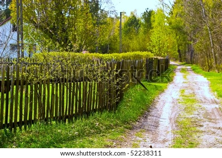 Old concrete boundary fence with nails on sunny day - stock photo