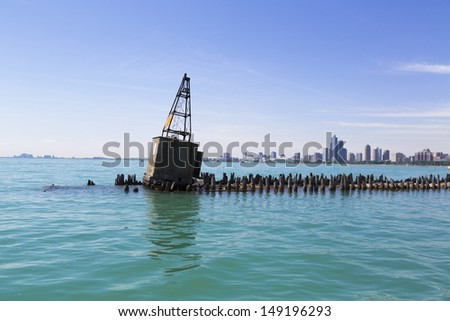 old concrete buoy on breakwater with Chicago skyline - stock photo