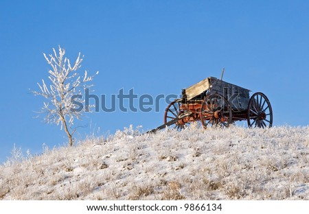 Old Conestoga Wagon on frosty prairie hill - stock photo