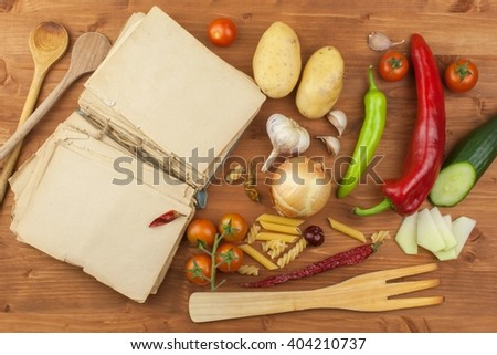 Old cookbook recipes on a wooden table. Cook healthy vegetable. Preparation of home diet food. Different kinds of vegetables. - stock photo