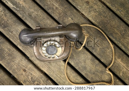 Old copper telephone on wooden surface - stock photo