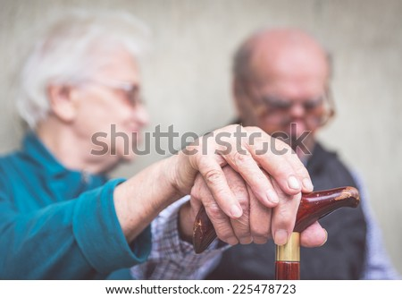 old couple. old man an woman still together holding each other hands over the man cane - stock photo