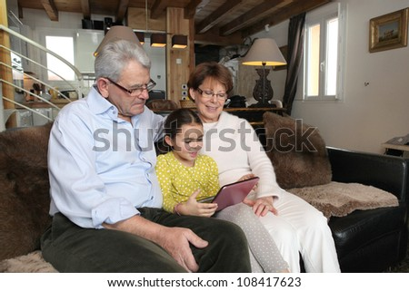 Old couple sat with their granddaughter - stock photo