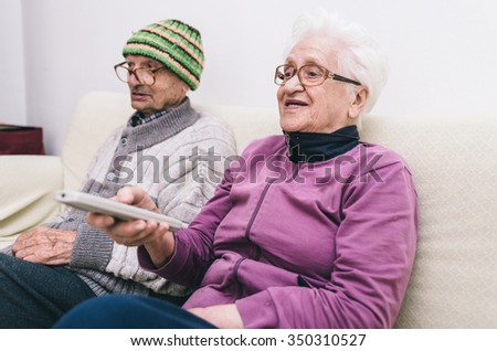 old couple watching television. man and woman sitting on the couch and making tv zapping - stock photo