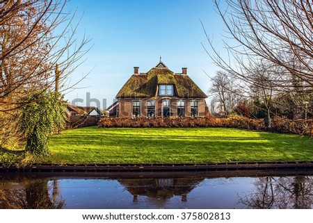 Old cozy house with thatched roof in Giethoorn, Netherlands. - stock photo