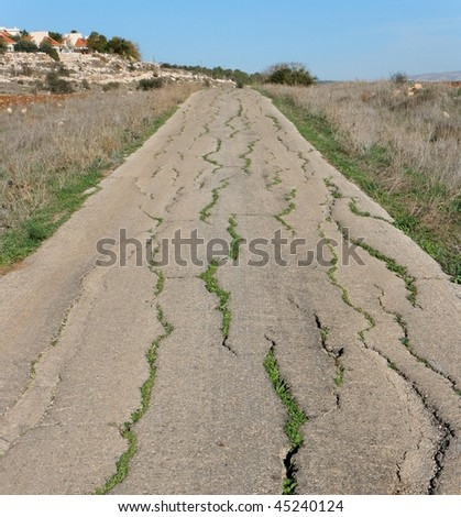 Old cracked countryside road in the evening - stock photo
