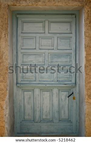 Old cracked light blue door - stock photo