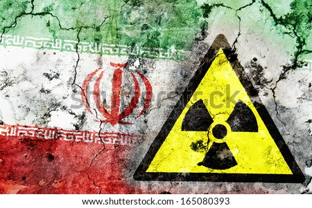 Old cracked wall with radiation warning sign and painted flag, flag of Iran - stock photo