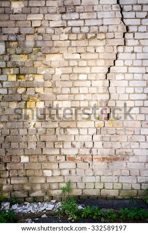 Old cracked white brick wall with green grass   - stock photo