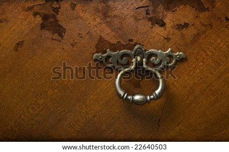 Old cracked wood background with gothic pewter or silver corroded door handle. - stock photo