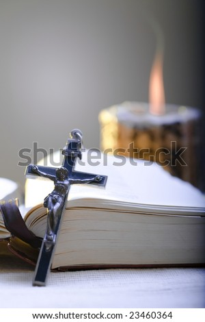 Old Cross and the Holy Bible laying on the table in fornt of a lighting candle. - stock photo