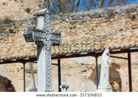 old cross carved in stone on a grave - stock photo