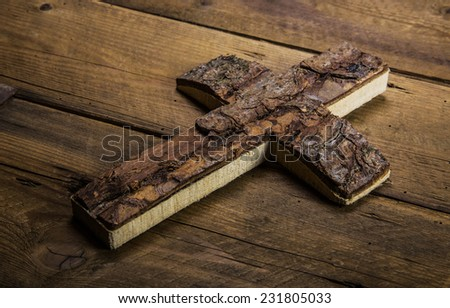 Old cross on wooden background for mourning or death concepts. - stock photo