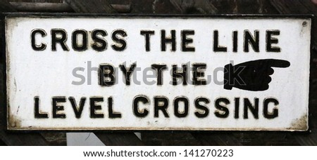 """Old """"cross the line by the level crossing"""" railway sign - stock photo"""
