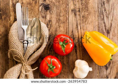 Old cutlery, surrounded by vegetables, wooden table. - stock photo
