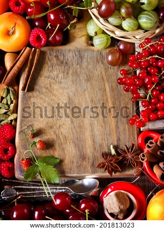 Old cutting board surrounded by fresh berries and spices with copy space for text. Vintage style. - stock photo