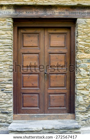 old dark brown wooden door and stone wall - stock photo