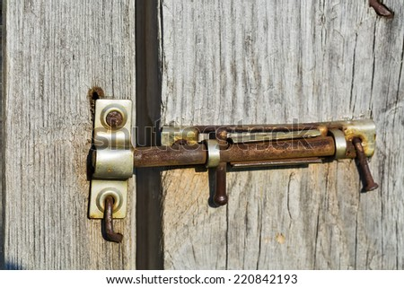 old deadbolt on wooden door - stock photo