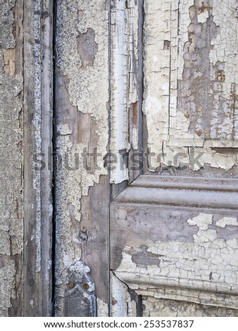 Old, decaying door with peeling white paint. - stock photo