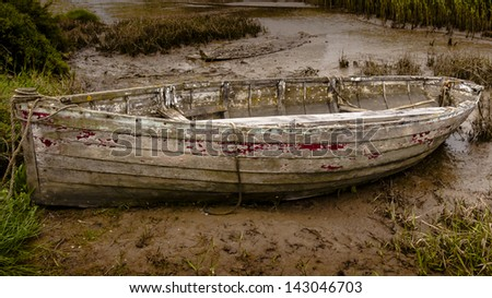 Old decaying rowing boat at Brancaster Norfolk England - stock photo